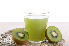 Fruit juice. A glass of kiwi juice with two halves of a kiwi fruit on both sides Stock Photography