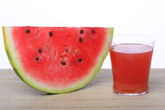 Fruit juice. A glass of purple watermelon juice and a thin slice of watermelon Stock Image