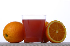 Fruit juice. A glass of red orange juice with half an orange and a couple of oranges around Stock Images