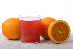Fruit juice. A glass of red orange juice with half an orange and a couple of oranges around Stock Photography