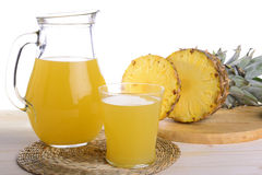 Fruit juice. A jug of pineapple juice and a glass of pineapple juice with slices of pineapple on a wooden tray Stock Image