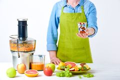 Fruit juice, pills and vitamin supplements. Woman holding glass full of pills standing next to juicer with loads of fresh fruit. Healthy lifestyle detox diet Royalty Free Stock Photography