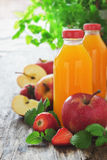 Fruit juice, ripe apples and strawberries Stock Images