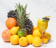 Fruit Juice In Wine Glass and Fresh Fruit. Glass of fresh fruit juice made with pineapple, grapes, grapefruit, oranges, lime and lemon Stock Image