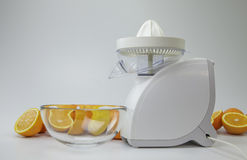 Fruit juicer and halfes of oranges Royalty Free Stock Photography