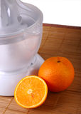 Fruit juicer and oranges Royalty Free Stock Photos