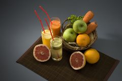 Fruit juices. Juice and fresh fruit on a table Royalty Free Stock Photos