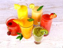 Fruit juices, kiwi, cherry, orange, strawberry, banana, pineapple Royalty Free Stock Photography