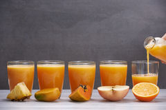 Fruit juices from pineapple, papaya, orange, mango and apple Royalty Free Stock Photos