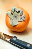Fruit kaki avec le couteau pour le couper dans les parts Images stock
