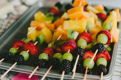 Fruit Kebab Tray. A tray of skewered strawberries, grapes, blackberries, kiwi, and melons Stock Photo