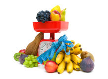 Fruit, kitchen scale and measuring tape on a white background Stock Photography