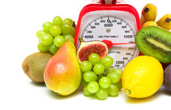 Fruit and kitchen scales close up on white background Royalty Free Stock Images