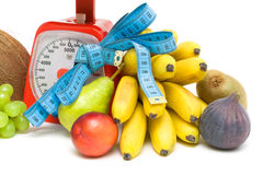 Fruit, kitchen scales and measuring tape close up. white backgro Royalty Free Stock Image