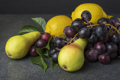 Fruit on  kitchen top like black grapes pears lemon. Fruit on the kitchen top like black grapes pears lemon Stock Images