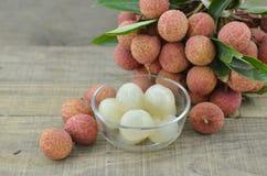 Fruit in kom en vers litchi op houten achtergrond wordt gepeld die Royalty-vrije Stock Afbeeldingen