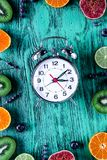 Fruit, lavender, blueberry mock-up with clock on blue desk backg Stock Photo