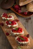 Fruit le plus brusque avec le fromage de framboise et blanc sur la BO en bois Photographie stock
