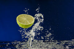 Fruit lime splash in water with bubbles Royalty Free Stock Photo