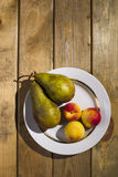 Fruit lying in a plate, standing on a wooden background. Stock Photos