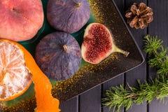 Fruit, mandarines, pin, figues sur la table noire Cadre sain de nourriture photo stock
