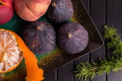 Fruit, mandarines, pin, figues sur la table noire Cadre sain de nourriture Photographie stock