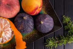 Fruit, mandarines, pin, figues sur la table noire Cadre sain de nourriture Photo libre de droits