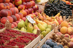 Fruit at the market. Variety of fresh fruit at the market. Pears, peaches, plums, raspberries, grapes and ginger in wooden boxes Royalty Free Stock Photos