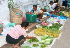 Female workers are active at the morning market,Luang Prabang,Laos. Women and a man are working at the morning fruits market in Asia, Laos, Luang Prabang Royalty Free Stock Image