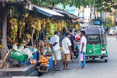 Fruit market. Fresh fruit stands. Galle, Sri Lanka. Fruit stalls in the street in Galle, Sri Lanka. Some locals talking. A green tuk-tuk on the right. Many Stock Images