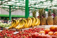 Fruit on the marketplace. Fresh colorful fruit in wooden baskets ready for sale on the marketplace in Belgrade. Pineapple and bananas royalty free stock images