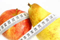Fruit with measuring tape Stock Images