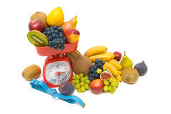 Fruit, measuring tape and kitchen scales close up on white backg Stock Image
