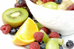 Fruit-Mix. White bowl with mixed fruits decorated with a kiwi half, an orange quarter, grapes and raspberries on the side Stock Photography