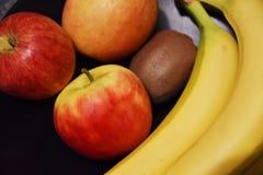 Fruit mix - bananas apples kiwis. Colorful mix of fruits on dark background - kiwi, banana, apples stock images