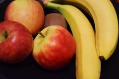 Fruit mix - bananas apples kiwis. Colorful mix of fruits on dark background - kiwi, banana, apples stock image