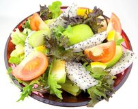 Fruit Mix Salad. In a bowl consist of Mesclun Mix, green apple, dragon fruits, tomatoes and lemon Stock Photos