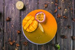 Fruit mousse cake with a mango and litchi decor on a wooden stand royalty free stock images