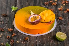 Fruit mousse cake with a mango and litchi decor on a wooden stand royalty free stock photo