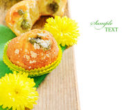 Fruit muffins with little yellow flowers on the table Royalty Free Stock Image