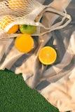 Fruit netto zak op de plaid op het gebied stock foto