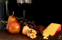 Fruit, Nuts, Cheese and Wine. A board with a bottle and glass of red wine, pear, walnuts, figs, grapes, and sharp cheese. Black background stock image