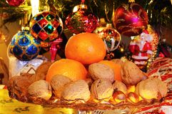 Fruit and nuts with Christmas tree to rear. Stock Photography