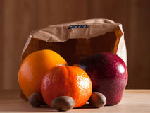 Fruit and Nuts. Orange, apple, and nuts coming from bag Stock Photo