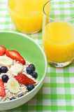 Fruit and Oat Breakfast. A breakfast setting with a bowl of fresh fruit and oats muesli and orange juice on a green and white gingham tablecloth Royalty Free Stock Images