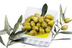 Fruit olive et feuilles imbibés en huile d'olive Photo stock