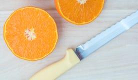 Fruit orange coupé en tranches avec le couteau photo libre de droits