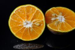 Fruit orange d'isolement sur le fond noir sain frais photos stock