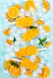 Fruit orange ice lolly on light blue background. Royalty Free Stock Photography