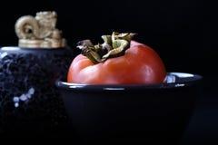 Fruit orange mûr de kaki d'un plat noir sur un fond noir, symboles bouddhistes, festival de récolte de Chusok photo stock